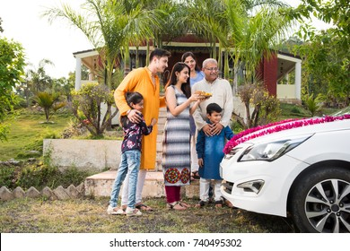 Indian Modern parents with kids welcoming new ca traditionally, performing Pooja