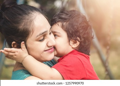 Indian Mother and Baby smiling together. Love. Happy cheerful family Mom and Baby girl kissing and hugging outdoor. Beautiful healthy mother and little daughter.Parenthood.