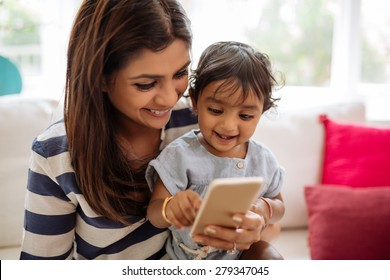 Indian mother and child playing game on the smartphone
