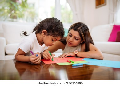 Indian mother and daughter drawing with crayons