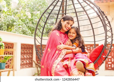 Indian mother and daughter hugging in hanging chair at home