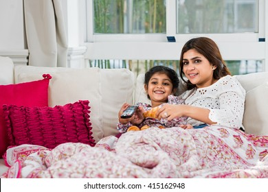 Indian mother and daughter lying on sofa and watching tv