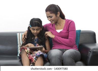 Indian Mother And Daughter Using digital touchpad At Home on sofa