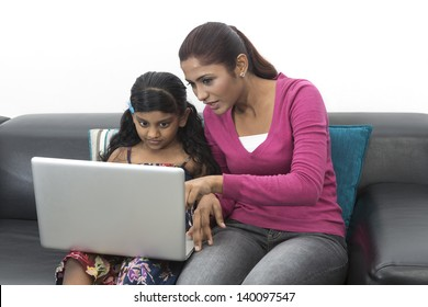 Indian Mother And Daughter Using Laptop At Home on sofa