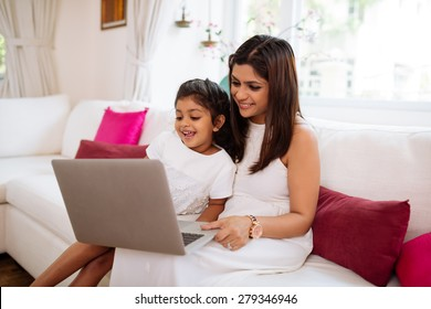 Indian mother and daughter watching something on laptop