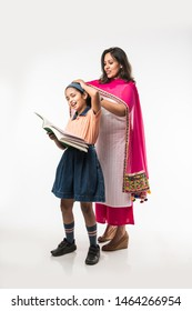 Indian Mother helping school girl with uniform getting ready with Lunch Box, hair style or waiting for school bus