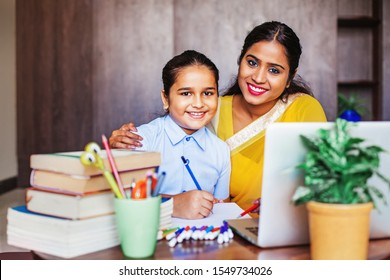 Indian mother and her daughter posing while doing homework with the help of laptop