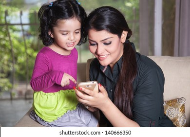Indian mother and her daughter using smart phone,