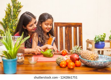 Indian mother and little daughter cooking vegetables together in a kitchen
