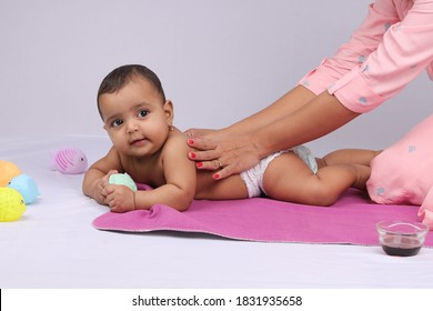 Indian Mother massaging her lovely baby.