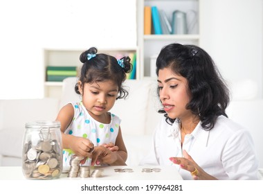 indian mother teaching daughter on financial planning indoor