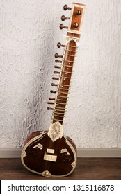 Indian musical instrument sitar standing next to the grey wall - image