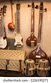 Indian musical instruments stringed guitars called sitars and Indian Folk percussion barrel shaped bass drums to produce classical music at market