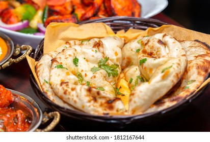 Indian naan bread on wooden table.