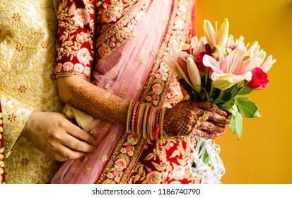 Indian Newlyweds Couple Hugging and bridal holding wedding flower bouquet