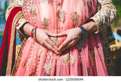 Indian newlyweds couple hugging and groom make heart shape on hand