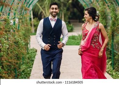 Indian newlyweds run under green arch in the garden