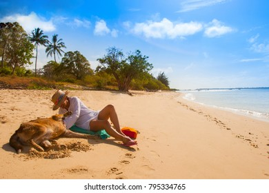 Indian Ocean. the city of Mombasa. Beach. Kenya A girl on the beach playing with a dog. A girl is stroking a dog. Sunny beach. 07.01.2006