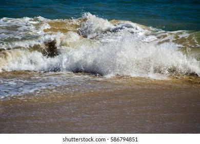 Indian Ocean waves breaking onto the soft wet  sandy shore  at  Ocean Beach Bunbury Western Australia on a fine morning in autumn creates a scenic seascape.