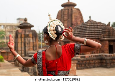 Indian Odissi classical dancer wears traditional costume and looks at the mirror