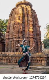 Indian Odissi dancer looks at the mirror at Mukteshvara Temple,Bhubaneswar, Odisha, India