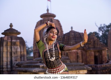 Indian odissi dancer striking pose against the backdrop of Mukteshvara Temple with sculptures in bhubaneswar, Odisha, India