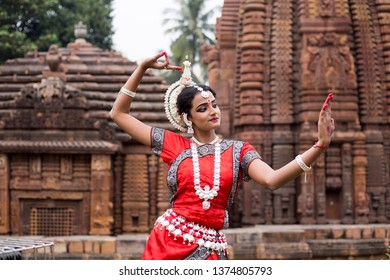 Indian Odissi dancer wears traditional costume and looks at the mirror