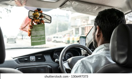 Indian OLA driver driving, right hand drive, picture from the back seat.