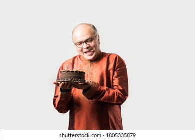 Indian old man celebrating own birthday by blowing candles on cake while wearing ethnic wear