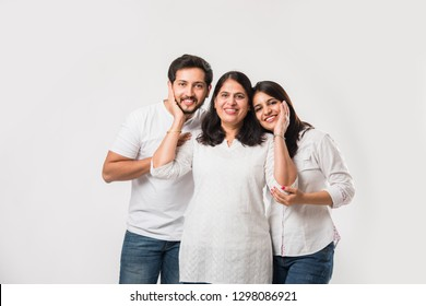 Indian old Mother embarrassing  young adult kids. Asian family of 3 standing isolated over white background. selective focus