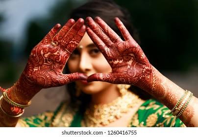 Indian Pakistani Bridal making heart shape and showing mehndi design Karachi, Pakistan, December 15, 2018