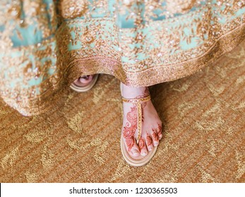 Indian Pakistani bride showing mehndi design on her foot sandals shoes