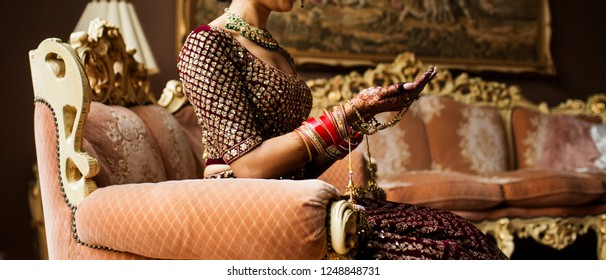 Indian Pakistani Bride sitting on sofa looking at Henna Mehndi Design on her hands.
