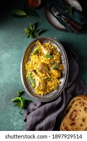 Indian or Pakistani food. Chiken Biryani rice biriany with mint herb and naan bread on green background.