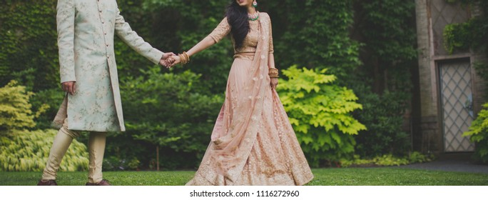 Indian Pakistani Newly Wed Couple holding hands and Walking Together .