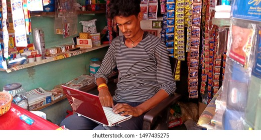 an indian pan shopkeeper operating laptop system at district Katni Madhya Pradesh in India shot captured on sep 2019