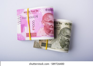 indian paper currency or money roll using new rupees 500 and 2000 notes, isolated over white background, selective focus