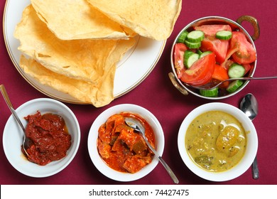 Indian pappadums with a tomato and cucumber salad and spicy pickles (from left): Andhra tomato  pickle, green mango pickle (or chutney) and white lime pickle