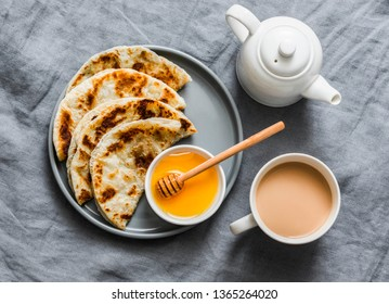 Indian paratha flatbread with honey and masala tea on grey background, top   view
