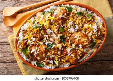 Indian pilaf biryani with chicken, onion, lemon, spices and cilantro close-up on the table. horizontal top view from above