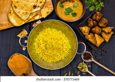 Indian pilau rice in balti dish served with chicken tikka masala curry, plain naan bread, vegetable samosas, and onion bhajis