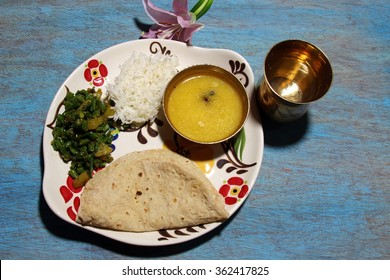 An Indian platter of lentil daal soup, chapati, rice and green beans curry with copy space on blue background.