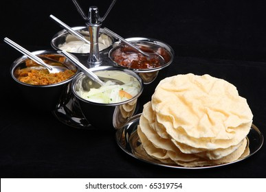 Indian poppadums with pickles, raita and onion salad.