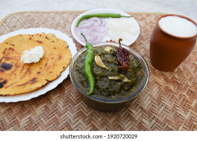 Indian popular dish makki di roti and Sarson da saag, mustard leaves curry and unleavened maize flour bread served in an authentic way with white butter and green chilly.Punjabi traditional style food