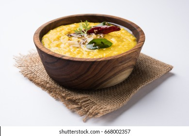 Indian popular food Dal fry or traditional Dal Tadka Curry served in a wooden bowl, isolated over white background, selective focus