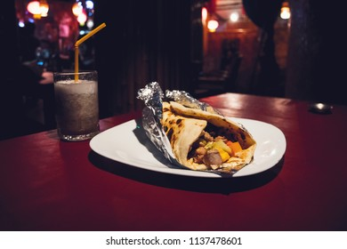 Indian popular snack food called Vegetable spring rolls or veg roll or veg franky made using paneer or cottage cheese and vegetables wrapped inside paratha chapati roti with tomato ketchup. milkshake