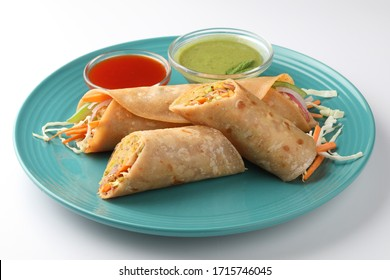Indian popular snack food called Vegetable spring rolls or veg roll or veg franky made using paneer or cottage cheese and vegetables paratha/chapati/roti with  tomato ketchup.