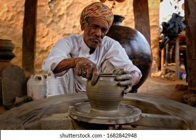 Indian potter at work: throwing the potter's wheel and shaping ceramic vessel and clay ware: pot, jar in pottery workshop. Experienced master. Handwork craft from Shilpgram, Udaipur, Rajasthan, India