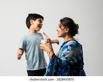 Indian pretty mother making her son drink milk in a glass