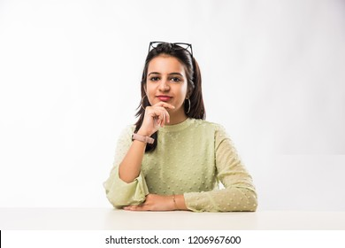 Indian pretty woman sitting at white table resting her chin on hand
